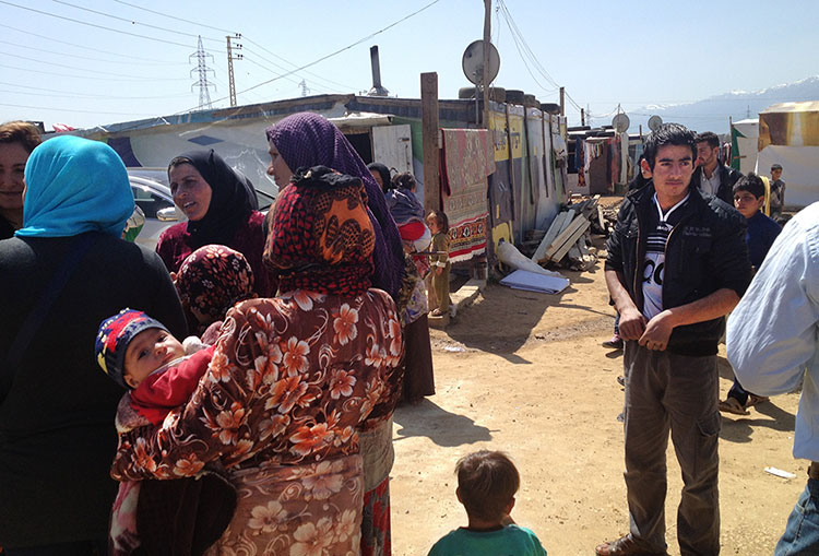 Syrian refugees standing and talking in shanty camps in the Lebanese Bekaa Valley. Credits: Bidna Capoeira