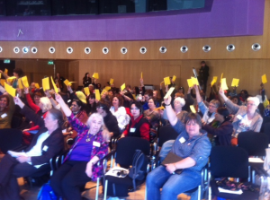WILPF members vote raise a yellow card to vote for the appoval of the WILPF 2015 Manifesto