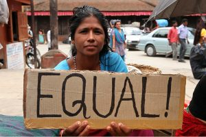 "Photo of women holding a sign with the words ""Equal"""